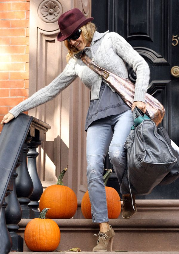 Actress Sarah Jessica Parker, dressed in a maroon fedora, gray sweater, jeans, and camel lace-up heels, carrying multiple bags, walks past several pumpkins on her stairs as she leaves for the airport on a chilly autumn day on October 03, 2010 in New York C