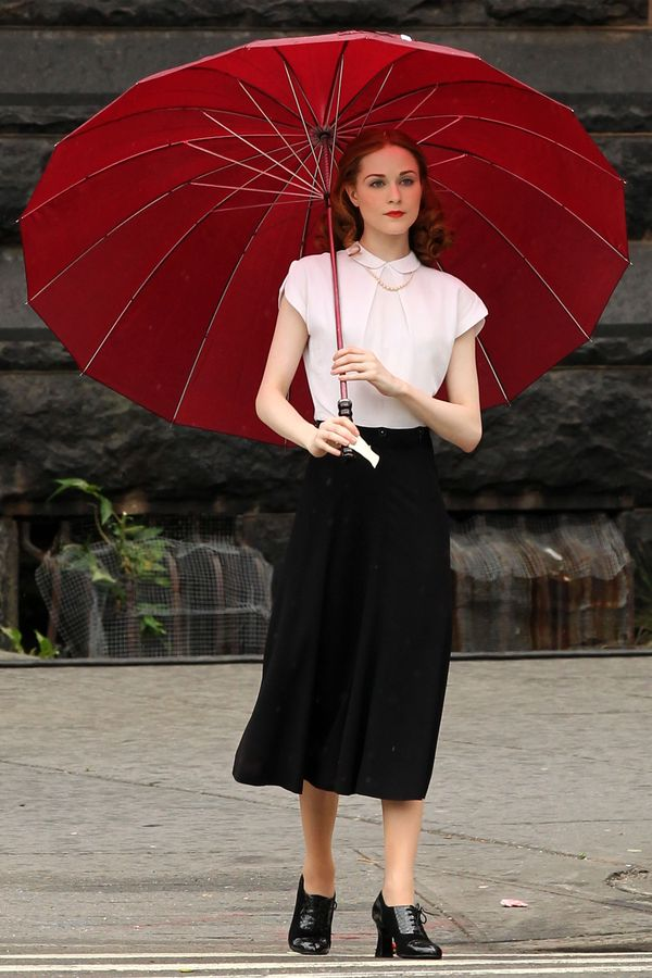 EXCLUSIVE: Actress Evan Rachel Wood, dressed in black knee-length skirt and white blouse, walks to her trailer with an umbrella on the set of her latest movie Mildred Pierce filming in Harlem in New York City, New York on June 1, 2010.