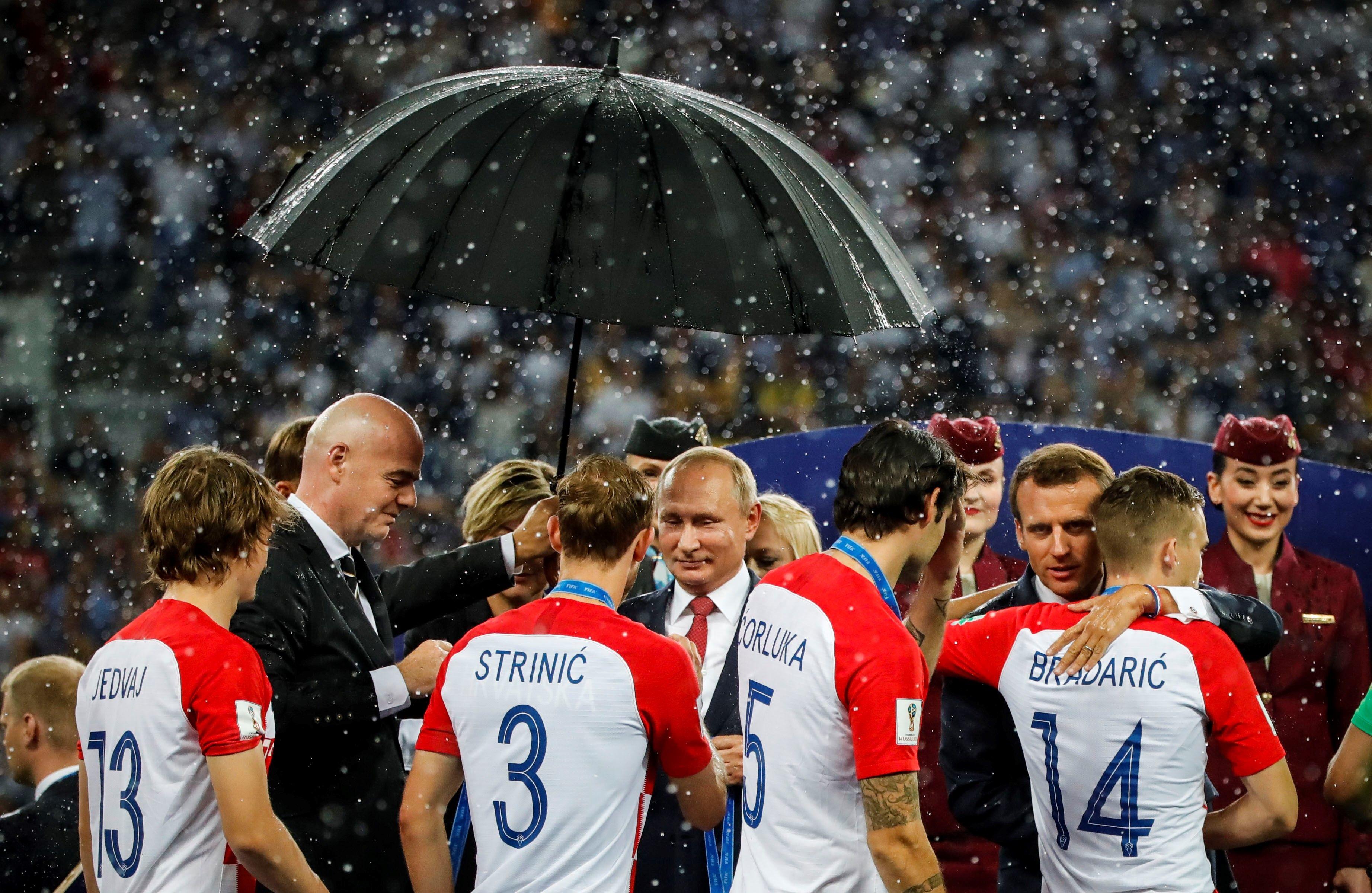 Lângă Vladimir Putin, Emmanuel Macron, Kolinda Grabar-Kitarović și Gianni Infantino suportă cu stoicism ploaia torențială.