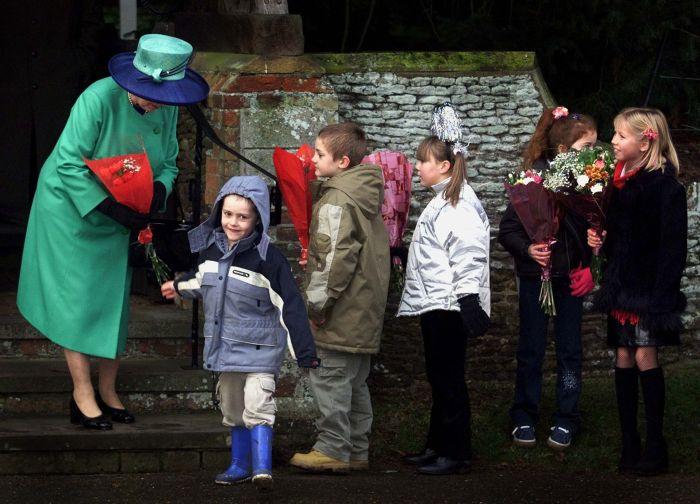 De Crăciun, Elisabeta a II-a primind daruri și felicitări de la copii, la biserica de la Sandringham.